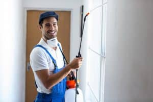 A smiling worker conducting some pest control in a house