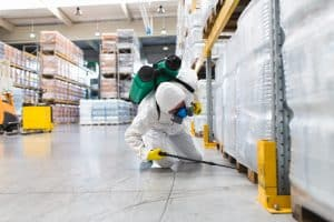 A worker conducting some pest control in a warehouse